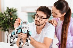 Een mens verzamelt een robot in de keuken De vrouw spreekt affectionately aan hem De man haalt weg het op royalty-vrije stock fotografie