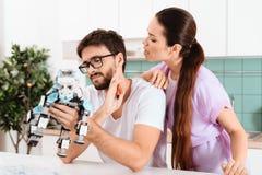 Een mens verzamelt een robot in de keuken De vrouw spreekt affectionately aan hem De man haalt weg het op royalty-vrije stock afbeelding