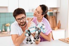 Een mens verzamelt een robot in de keuken De vrouw spreekt affectionately aan hem De man haalt weg het op stock foto's