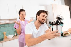 Een mens verzamelt een robot in de keuken Zijn meisje is achter hem en zeer boos royalty-vrije stock foto's
