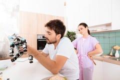 Een mens verzamelt een robot in de keuken Zijn meisje is achter hem en zeer boos stock foto