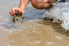 Een mens ving een mooie krab in de stormachtige golven van de Zwarte Zee stock afbeeldingen