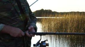 Een mens vist van een boot op zonsondergang stock videobeelden