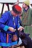 Een mens voedt een babyvarken Stock Foto