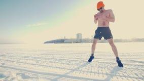 Een mens voert uitrekkende oefeningen in de winter uit stock video