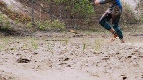 Een mens in een vuil ras loopt in een modderige vulklei stock videobeelden