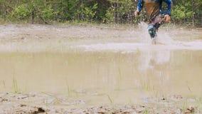 Een mens in een vuil ras loopt in een modderige vulklei stock video