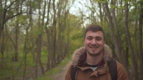 Een mens in een warm brounjasje loopt door het hout De man gaat vooraan, volgt de camera van hem stock video