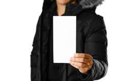 Een mens in een warm de winterjasje die een wit pamflet houden Leeg document Sluit omhoog Geïsoleerdj op witte achtergrond royalty-vrije stock afbeeldingen