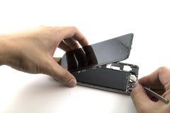 Een mens was hersteller He voorbereidingen treft aan mobiele telefoonreparatie hij trekkracht Verzegelende band was om de batteri Royalty-vrije Stock Afbeeldingen