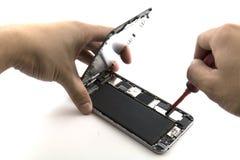 Een mens was hersteller He voorbereidingen treft aan mobiele telefoonreparatie hij verandering mobiele telefoonbatterij was Stock Afbeelding