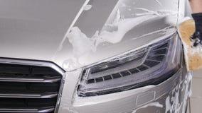Een mens wast autokoplampen Concept handautowasserette stock footage