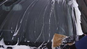 Een mens wast het autoglas Concept handautowasserette stock footage