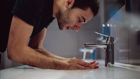Een mens wast zijn handen en gezicht stock video