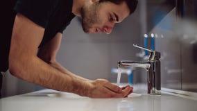 Een mens wast zijn handen en gezicht Langzame Motie stock footage
