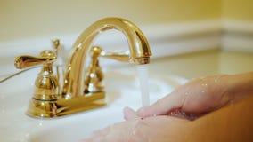Een mens wast zijn handen onder een vergulde kraan stock videobeelden