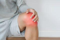 Een mens wat betreft knie met rood benadrukt concept knie en gezamenlijke pijn royalty-vrije stock afbeeldingen