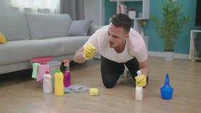 Een mens is weerzinwekkend wanneer hij een reusachtig insect terwijl schoonmakend vindt stock video
