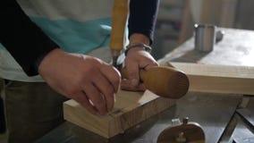 Een mens werkt een beitel en een houten hamer stock video