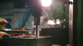 Een mens werkt met een boor voor metaal Het voegt vloeistof aan het materiaal toe stock videobeelden
