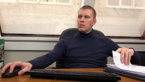 Een mens werkt met documenten en een computer bij zijn bureau stock video
