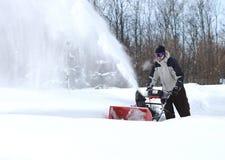 Een mens werkt sneeuw blazende machine stock fotografie