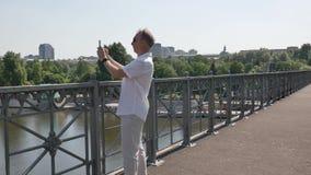 Een mens in een wit kostuum fotografeert mooie cityscape op een smartphone stock footage