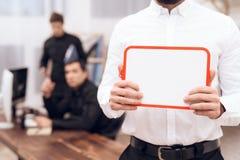 Een mens in een wit overhemd bevindt zich met een witte raad in zijn handen stock fotografie