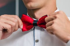 Een mens in een wit overhemd bindt een rode vlinderdas terwijl het voorbereidingen treffen voor een huwelijksceremonie stock foto