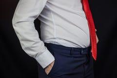 Een mens in een wit overhemd en band met een bloated maag stock afbeeldingen