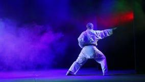 Een mens in een witte kimono is bezig geweest met karate stock video