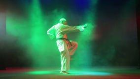 Een mens in een witte kimono is bezig geweest met karate tegen een achtergrond van rook stock video