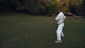 Een mens in witte kimono het praktizeren karate, die katacombinaties in de ochtend op open plek in het stadspark uitvoeren stock videobeelden