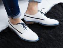 Een mens in witte modieuze die schoenen van zacht leer worden gemaakt stock foto