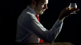 Een mens in een witte overhemd en een band met een baard bekijkt een glas van alcohol en denkt, zwarte achtergrond, degustation stock video