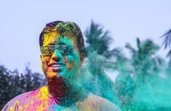 Een mens worden die die met holikleuren tijdens holifestival wordt overgoten in India stock afbeeldingen