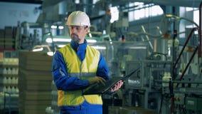Een mens in workwear inspecteert productieproces van plastiek stock footage