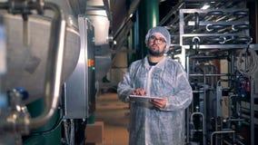 Een mens in workwear maakt berekeningen op zijn tablet in een distilleerderijfaciliteit stock videobeelden