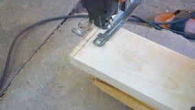 Een mens zaagt een houten bar met een elektrische figuurzaag De bouwer werkt met een elektrische zaag in de binnenplaats van stock video