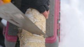 Een mens zaagt een logboek met een handzaag in de winter Close-up stock video