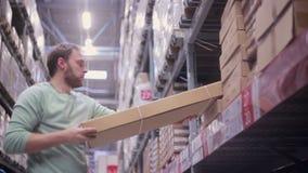 Een mens zet dozen op de planken in een pakhuis terug en gaat vanaf de camera stock footage
