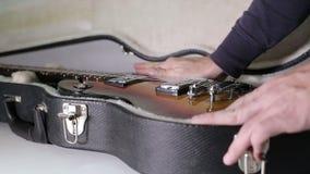 Een mens zet een gitaar in het geval stock footage