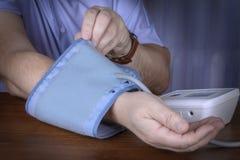Een mens zet op een apparaat om bloeddruk te meten stock afbeeldingen