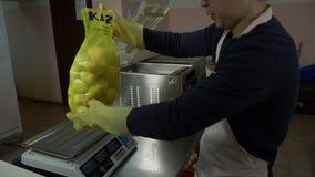 Een mens zet een pakket van aardappels in een vacuümverpakker stock video