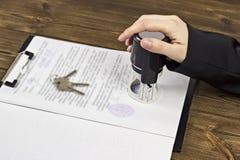 Een mens zet een verbinding op documenten wanneer het kopen van een flat, de sleutels aan het flatcontract stock afbeelding