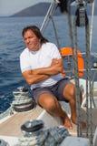 Een mens zit aan boord van zijn varend jacht Sport Royalty-vrije Stock Afbeeldingen