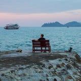 Een mens zit alleen op een steenklip van de overzeese kust in de schemering Royalty-vrije Stock Afbeelding