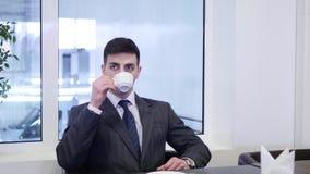 Een mens zit bij een lijst in de koffie en de drank coffe stock video