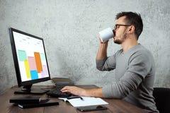 Een mens, een mens zit bij een lijst in het bureau en drinkt koffie, een onderbreking Concept voor het bureauwerk, lunch, onderbr stock afbeelding