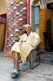 Een mens zit buiten zijn tapijtwinkel in Meknes, Marokko stock foto